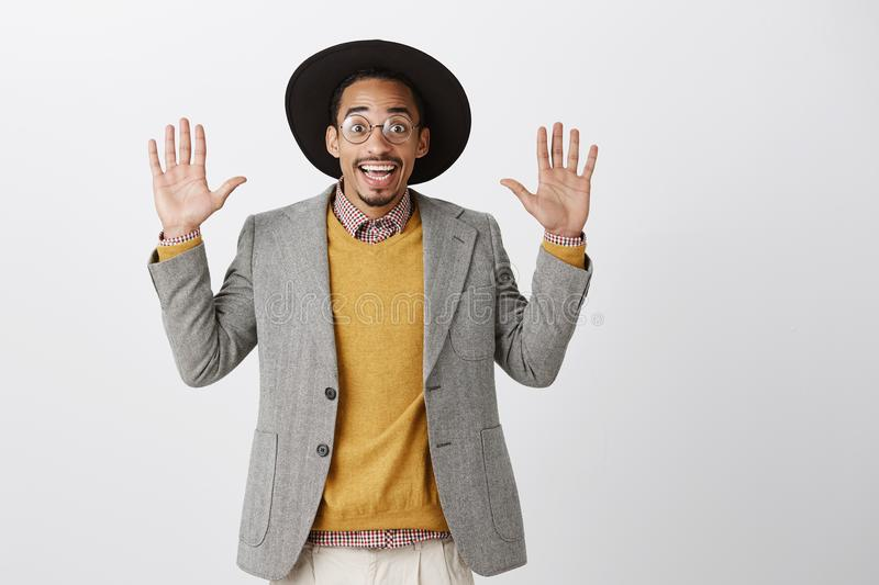 Coworker being caught on stealing food. Portrait of funny good-looking african guy in trendy black hat and stylish stock photos