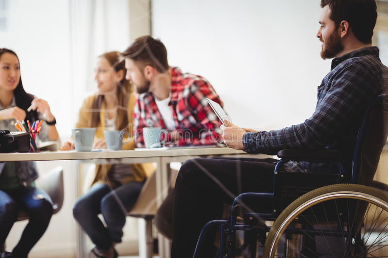 Coworker on wheelchair using digital tablet against photo editors. In meeting room at creative office royalty free stock image