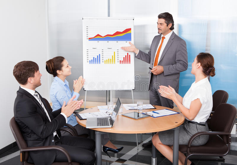 Coworkers applauding businessman stock photography