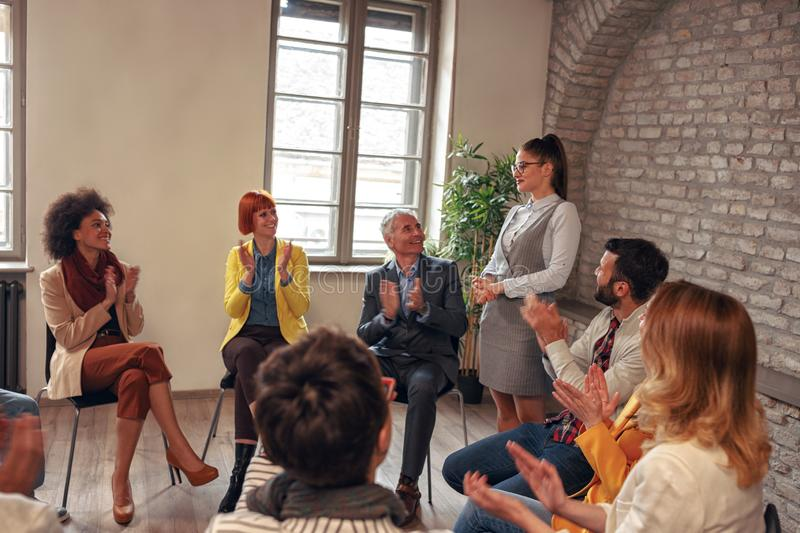 Coworkers applauding woman in group meeting royalty free stock photos
