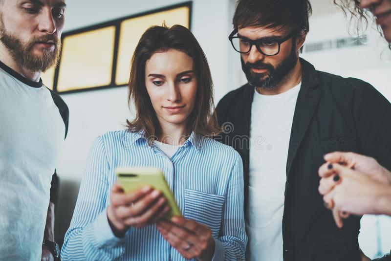 Coworkers business meeting concept.Young women holding mobile smartphone hand and showing information to her colleagues stock photos