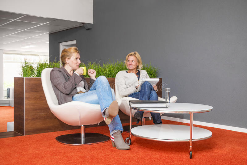 Coworkers drinking coffee at the office stock image