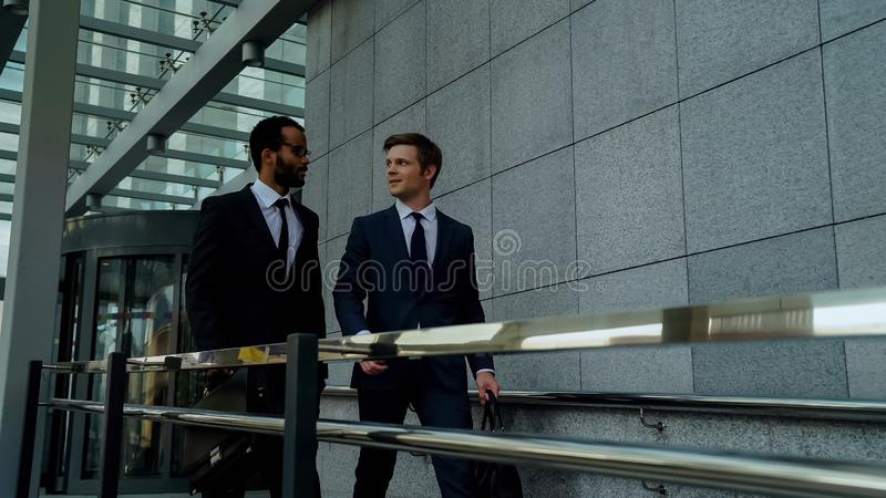 Coworkers leaving work together, sharing plans on weekend in conversation royalty free stock image