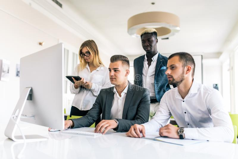 Coworkers looking at a computer and talking about work in modern office stock photos