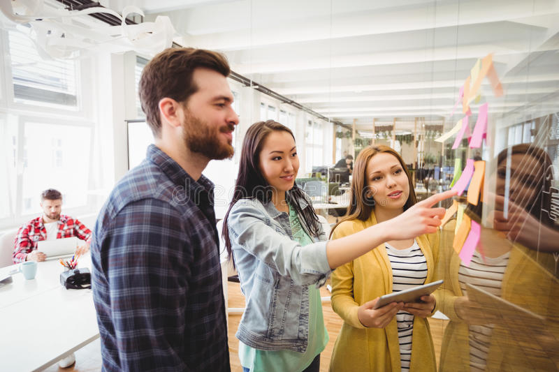 Coworkers looking at sticky notes pointed by female photo editor stock photos