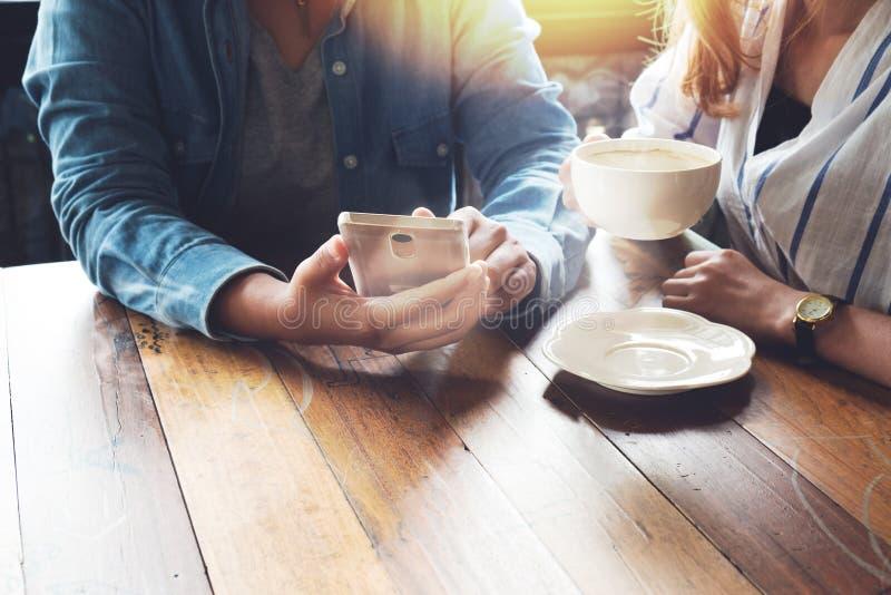 Coworkers młode kobiety pracuje w kawiarni z mądrze telefonem biznesowa praca zespołowa fotografia stock