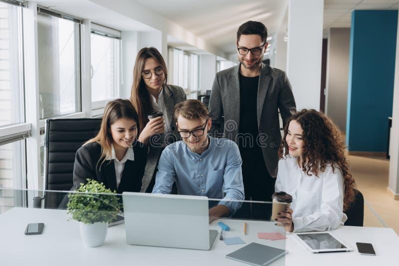 Coworkers patrzeje komputer i opowiada prac? obraz royalty free
