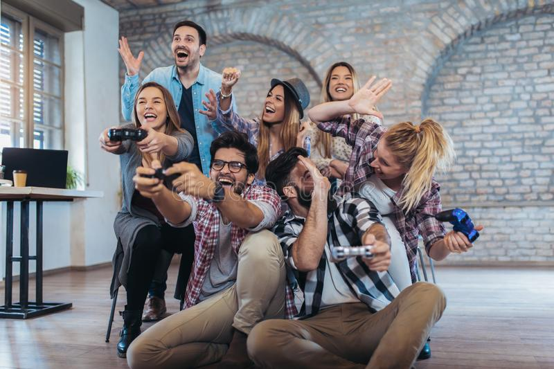 Coworkers playing video games in office. Coworkers playing video games in modern office stock photography