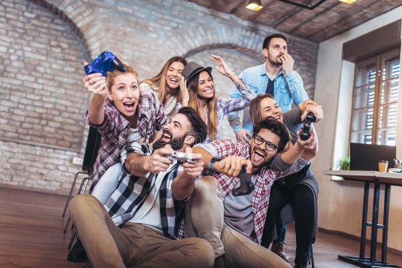 Coworkers playing video games in office. stock image