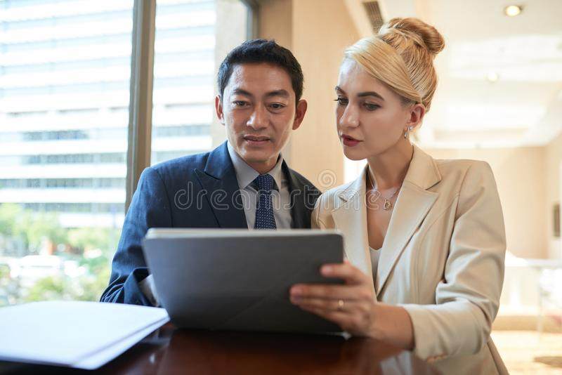 Coworkers reading data on tablet royalty free stock photography