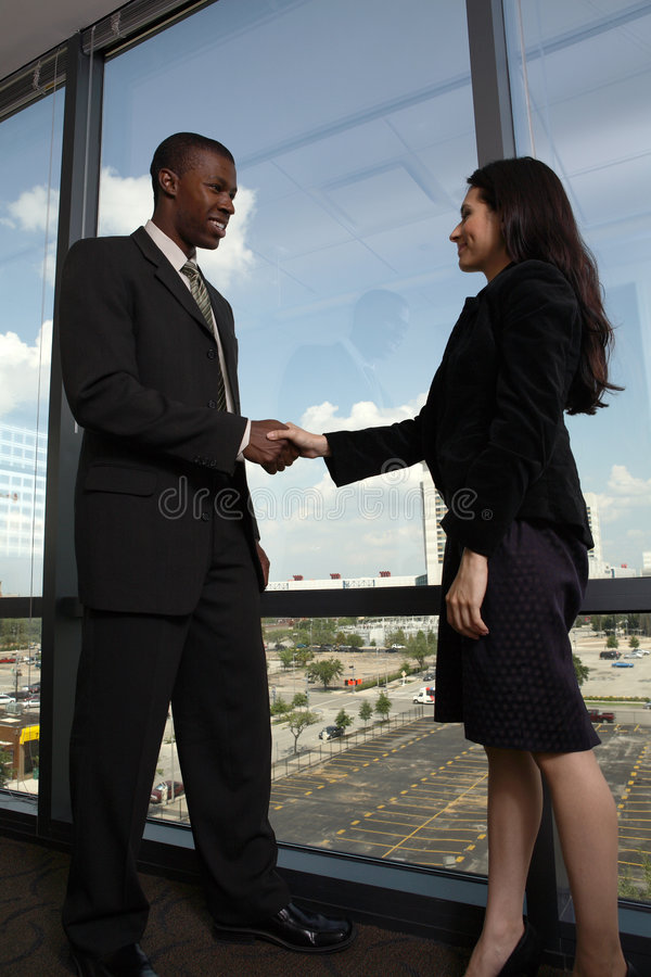 Coworkers shaking hands stock images