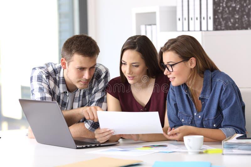 Coworkers som arbetar på kontoret som jämför data royaltyfria bilder