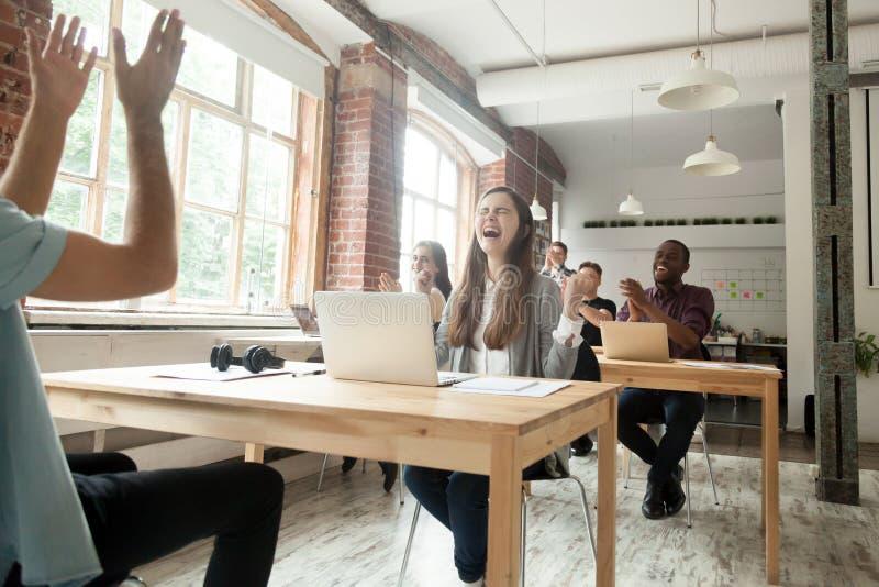 Coworkers som firar enorm prestation i delat kontor royaltyfri fotografi