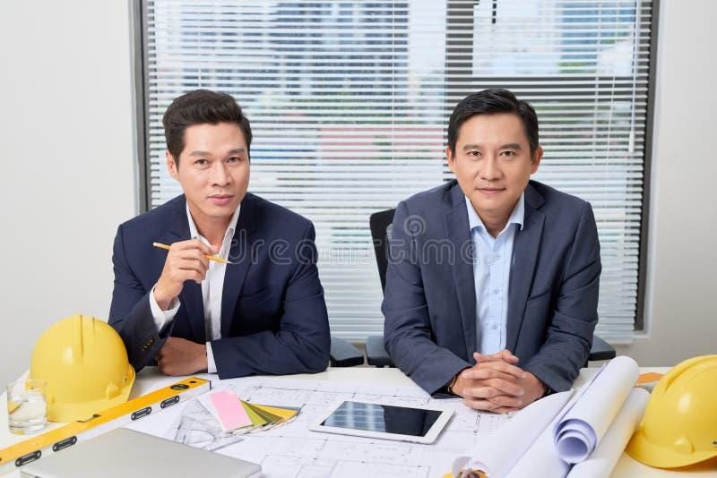Coworkers som i regeringsställning arbetar Affärsfolk som planerar över skrivbordet royaltyfri fotografi