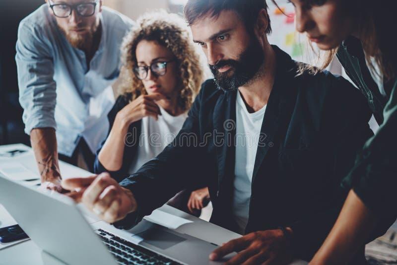 Coworkers som tillsammans arbetar i modernt kontor Skäggig man som talar med kollegan och använder bärbara datorn, medan sitta på royaltyfri bild