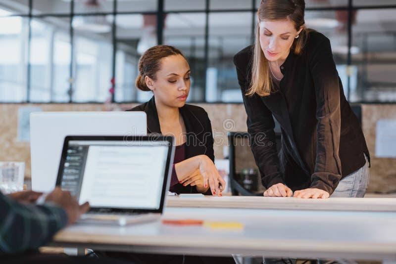 Coworkers som tillsammans går till och med skrivbordsarbete royaltyfria bilder