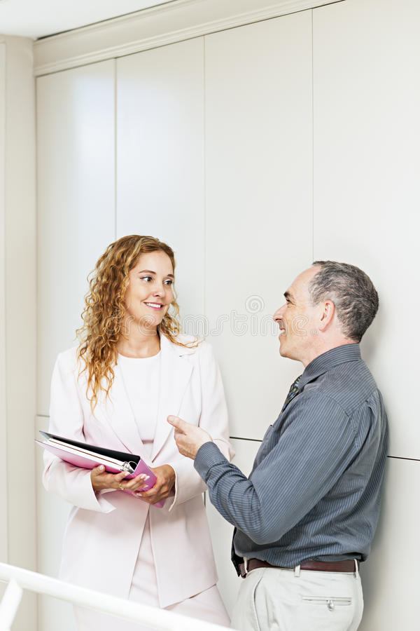 Coworkers talking in hallway stock photos