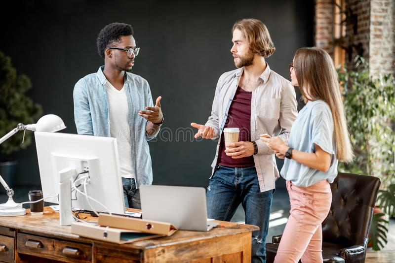 Coworkers talking together at the office stock photo