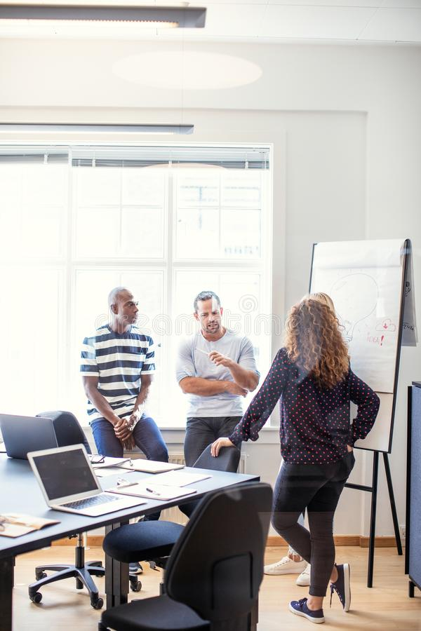 Coworkers talking together in an office after a meeting royalty free stock images