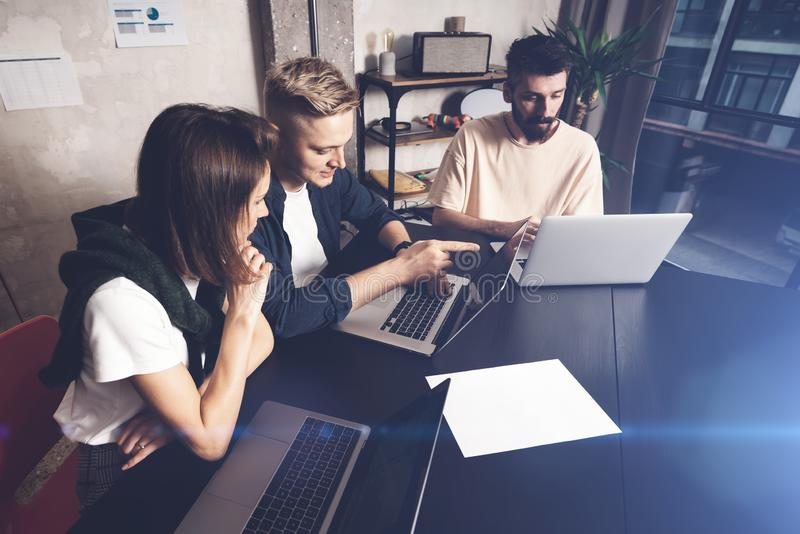 Coworkers team at work. Group of young business people in trendy casual wear working together in creative office royalty free stock photo