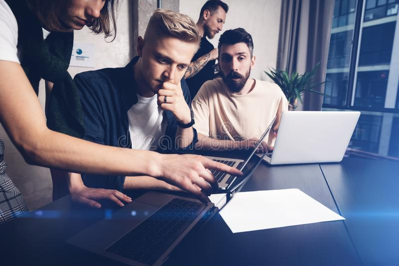 Coworkers team at work. Group of young business people in trendy casual wear working together in creative office royalty free stock photography