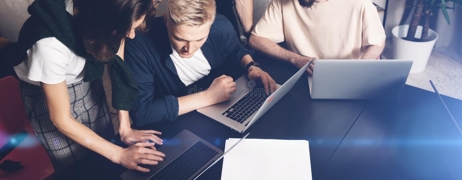 Coworkers team at work. Group of young business people in trendy casual wear working together in creative office.Wide. Coworkers team at work. Group of young royalty free stock photo