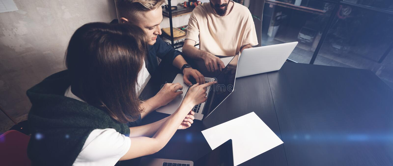 Coworkers team at work. Group of young business people in trendy casual wear working together in creative office.Wide royalty free stock images