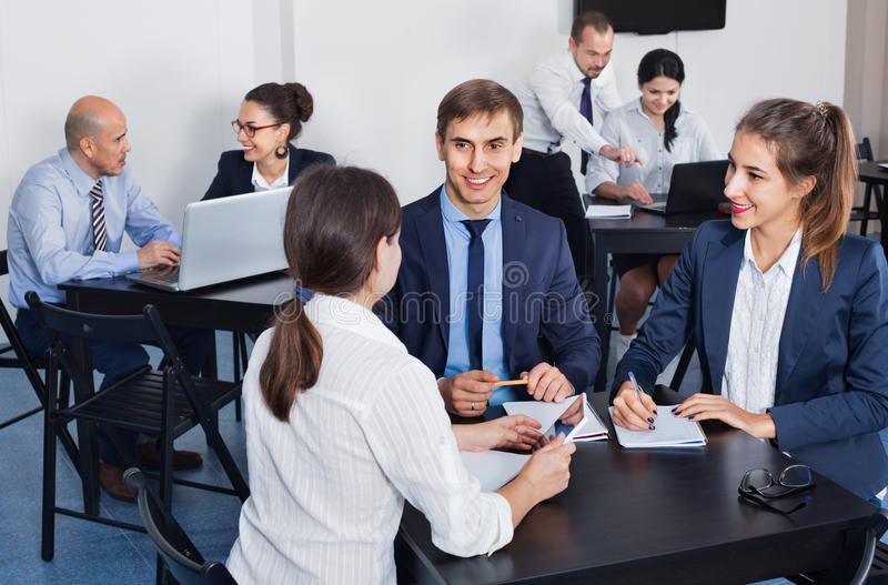 Coworkers working effectively on business project together. Positive coworkers working effectively on business project together stock image