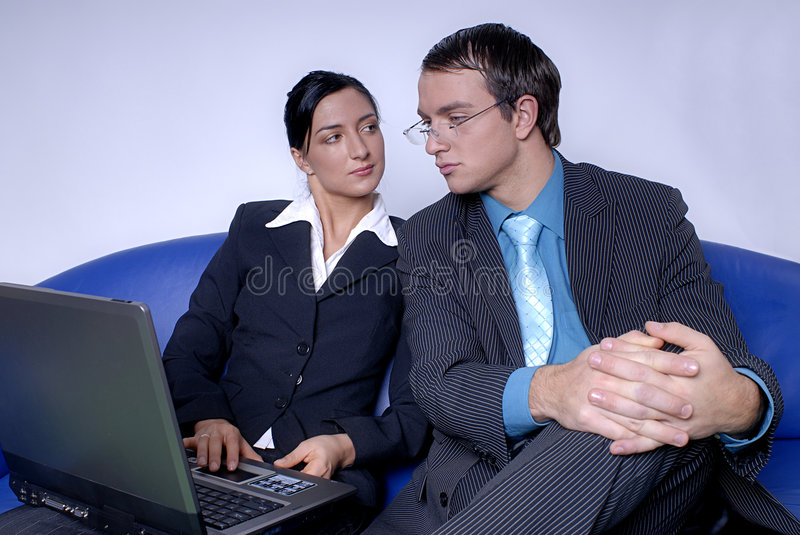 Coworkers working on laptop stock image