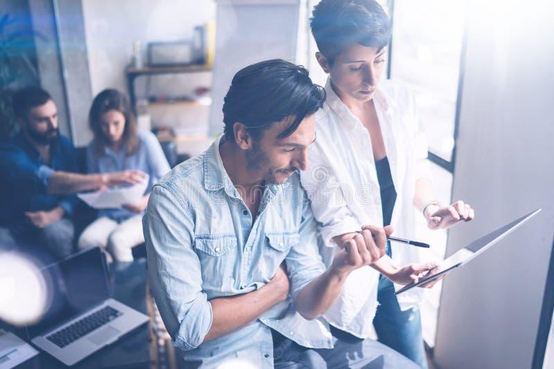 Coworking队会议 小组两businessmans与新的起始的项目一起使用在现代办公室 在妇女的触摸板 库存照片