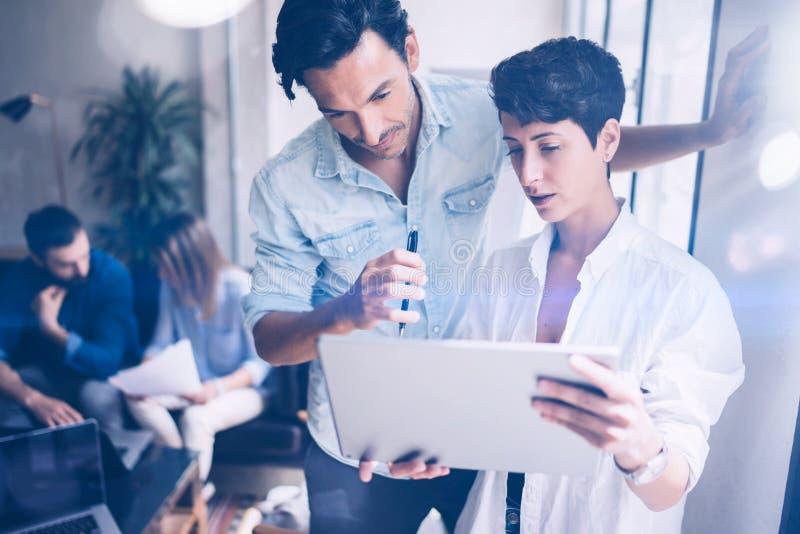 Coworking队会议 小组businessmans与新的起始的项目一起使用在现代办公室 报告在妇女手上 免版税图库摄影
