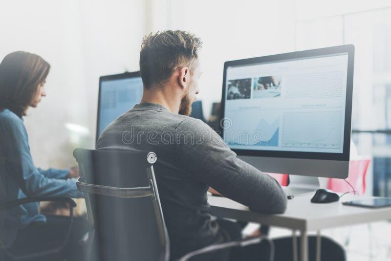 Coworking队过程 照片年轻企业乘员组与新的起始的项目现代办公室一起使用 台式计算机 免版税库存照片