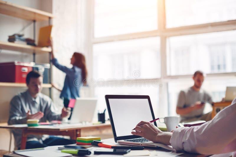 Coworking驻地 现代企业顶楼和的millenials 空白膝上型计算机键入 免版税库存照片