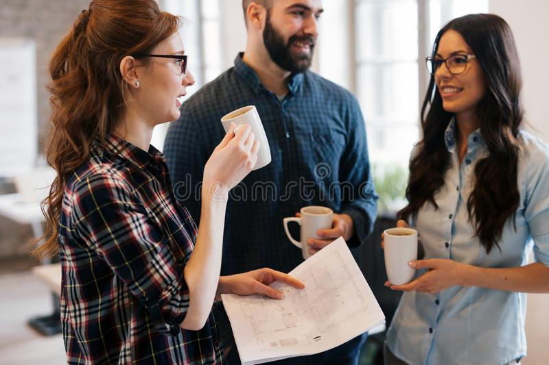 Coworking colleagues having conversation at workplace stock photography