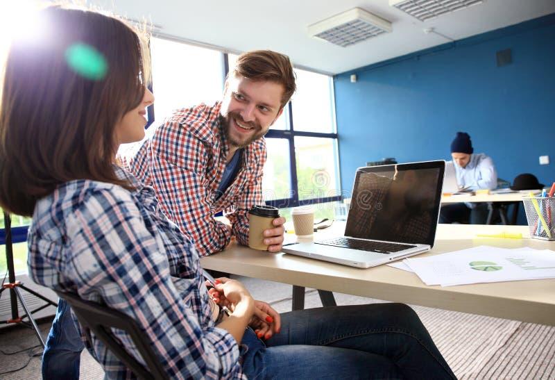 Coworking procesa, equipo de los diseñadores que trabaja la oficina moderna Encargado creativo joven de la foto que muestra el nu imagen de archivo libre de regalías