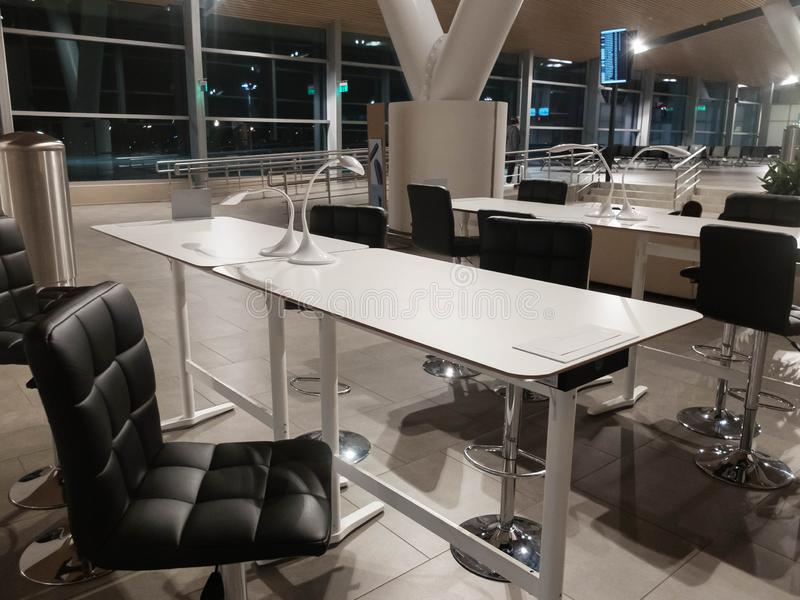 Coworking zon p? flygplatsen Vita lampor p? det vita skrivbordet, svarta stolar arkivfoton