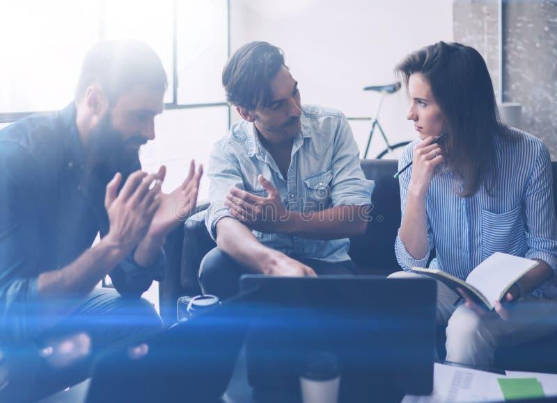Coworkingsproces in een zonnig bureau Jongeren die het bespreken maken op kantoor Commerciële teamzitting op de bank en het gebru stock afbeelding