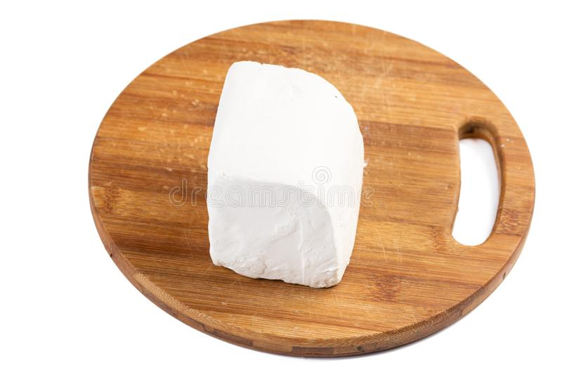 Cows white cheese sliced on the kitchen cutting wooden board royalty free stock photo
