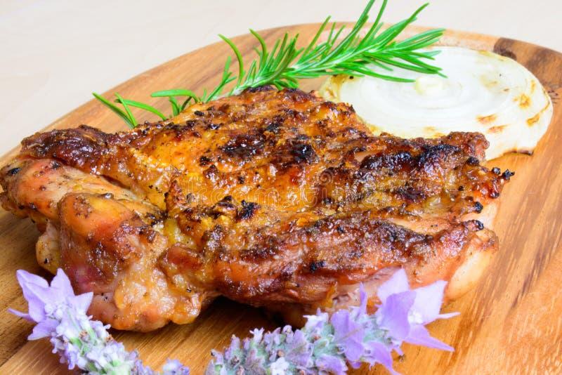 A coxa de frango sem ossos grelhada BBQ com fatia da cebola e com alecrins e a alfazema decoram fotos de stock royalty free