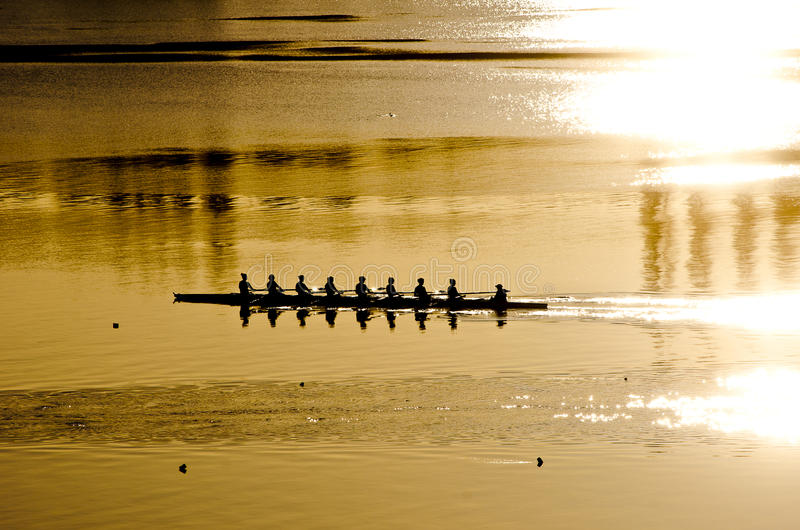 Rowing crew at sunrise royalty free stock photography