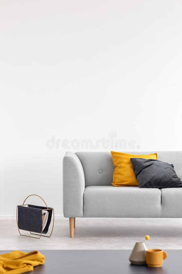 Coxim amarelo e preto no sofá cinzento no interior branco do sótão com espaço da tabela e da cópia Foto real fotografia de stock