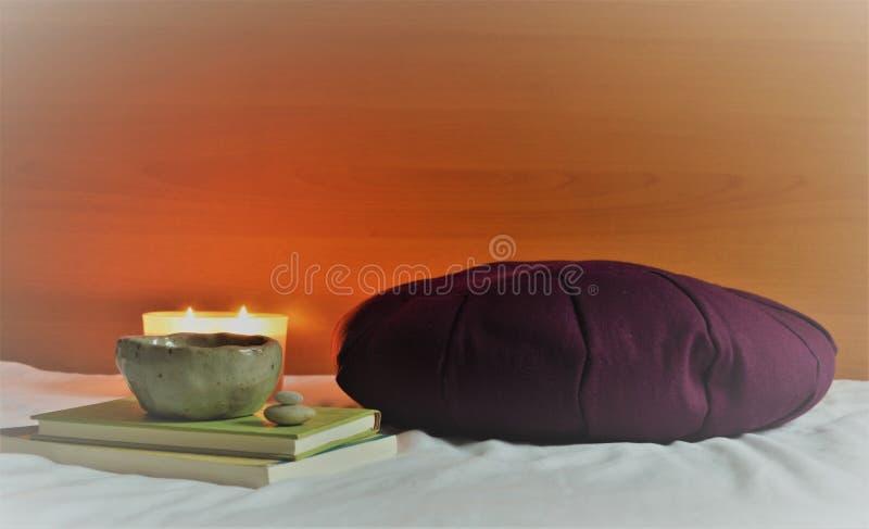 Coxim da meditação com luz e livros da vela fotos de stock