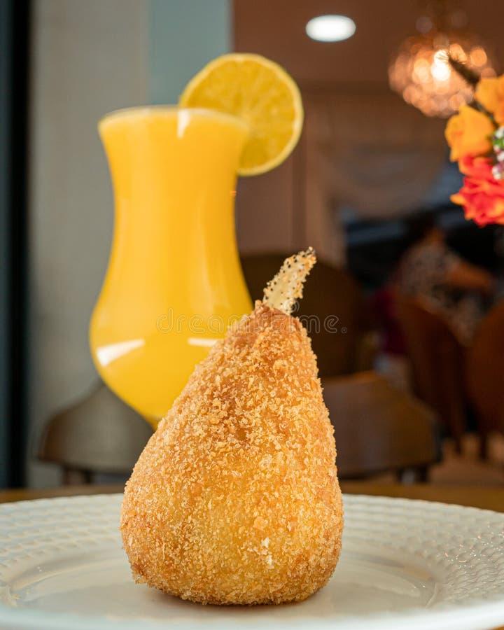 Coxinha del cangrejo, bocados brasileños tradicionales, zumo de naranja imagen de archivo