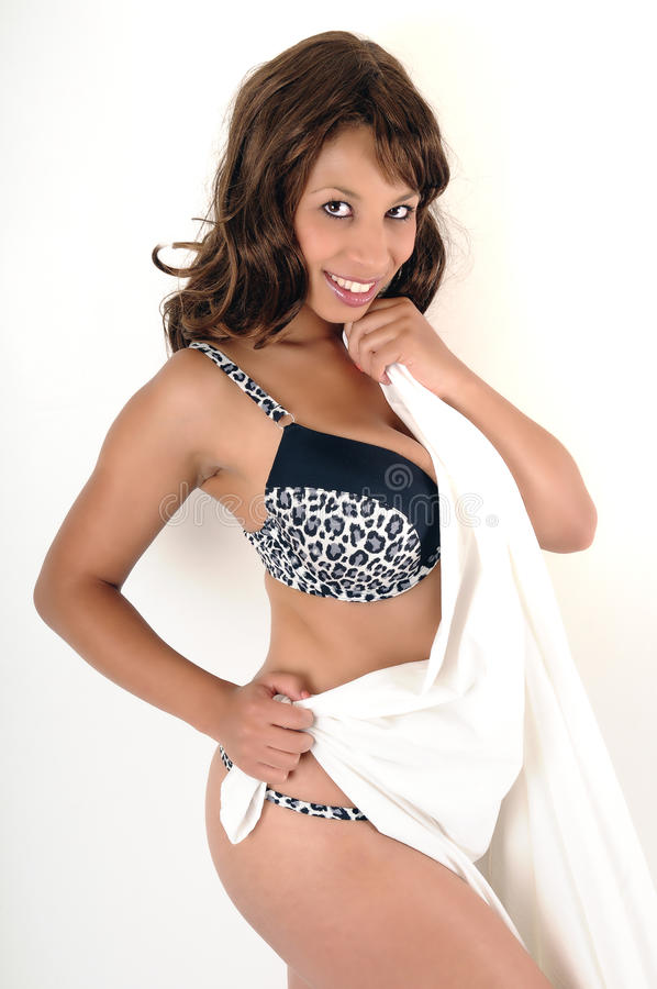 Coy !. Beautiful girl with long flowing hair and large breasts, wearing a black and leopard print bra, while holding a white towel royalty free stock image