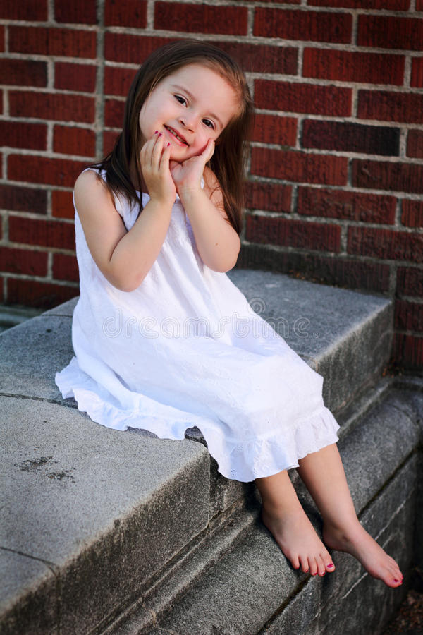 Coy little 2 year old. A closeup of a barefooted coy little girl in a white summer dress sitting by a brick wall. Shallow depth of field royalty free stock images