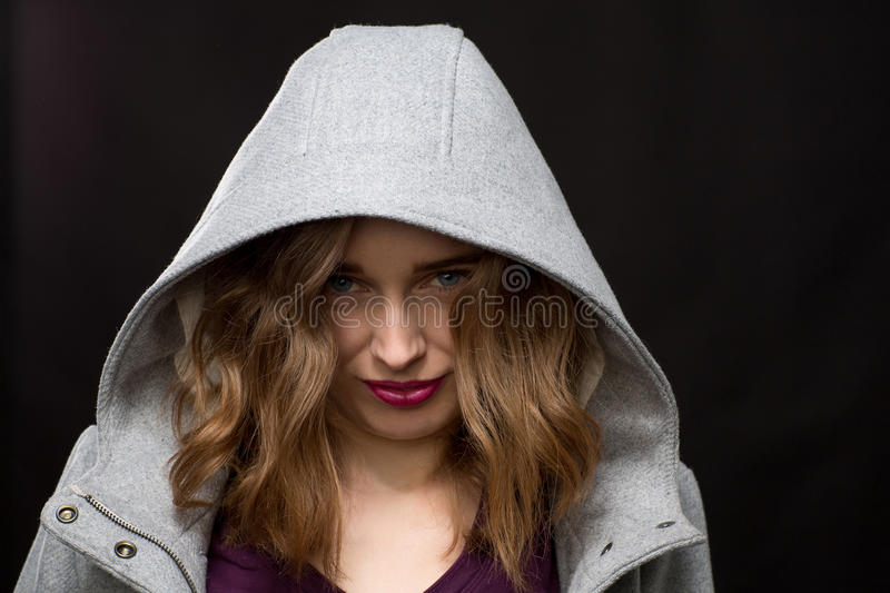 Coy or shy young woman wearing a hood. Peering out at the camera with her head down against a dark background royalty free stock images