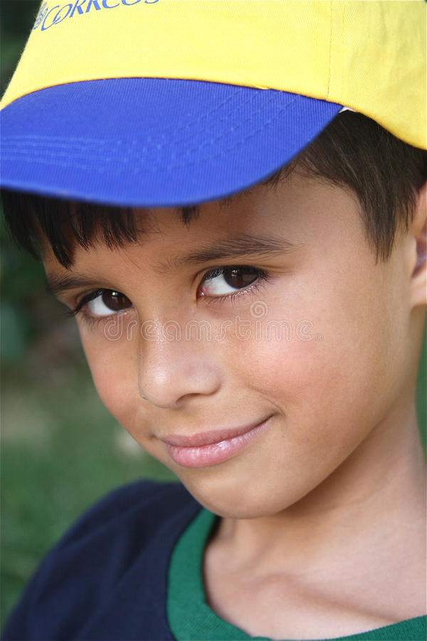 Coy Summer Boy. Coy boy smiling with yellow hat royalty free stock photos