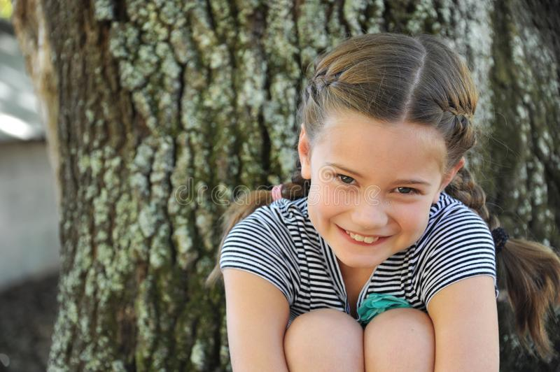 Coy and Sweet Little Girl. Beautiful little girl, with braided hair, peeks up at the camera. She is sitting outdoors besides an oak tree royalty free stock image