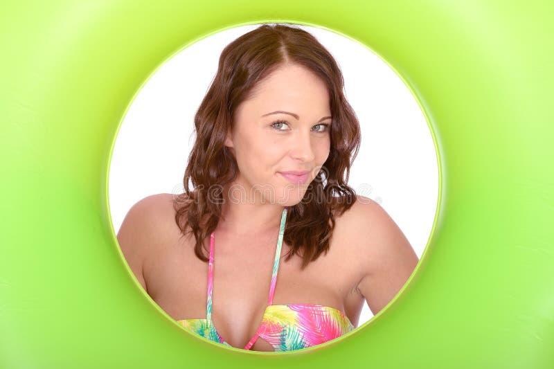 Coy Young Woman Looking Through insolente atrativo um anel de borracha verde fotos de stock royalty free