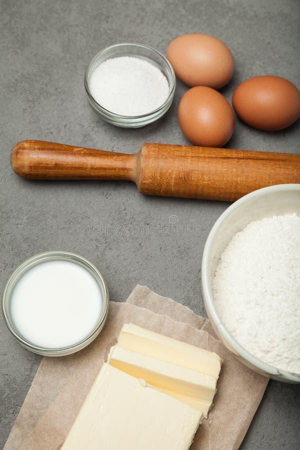Coza o cozinheiro com ferramentas e ingredientes da cozinha: farinha, ovos, manteiga, açúcar imagem de stock royalty free
